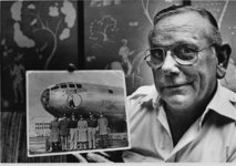 File - Charles Donald Albury holds a picture of the B-29 bomber 'The Great Artiste' and it's crew in this Oct. 1980 file photo.