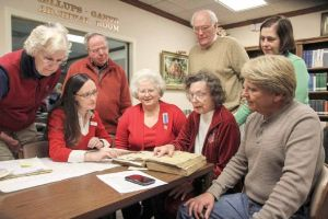 Mary Ann McCollum of Birmingham, Ala., points to records contained in the Wiatt Randle family Bible donated to the Columbus-Lowndes Public Library Nov. 14. Looking on, seated from left, are library archivist Mona Vance-Ali, Bernard Romans DAR Regent Alice Lancaster and Randle family relative Mark Gaines Miles of Jacksonville, Fla. Standing, from left, are family members Chuck and Kitty Edwards of Florence, Ala., and Dan and Carol Randle of Chattanooga, Tenn. Photo by: Micah Green/Dispatch Staff.